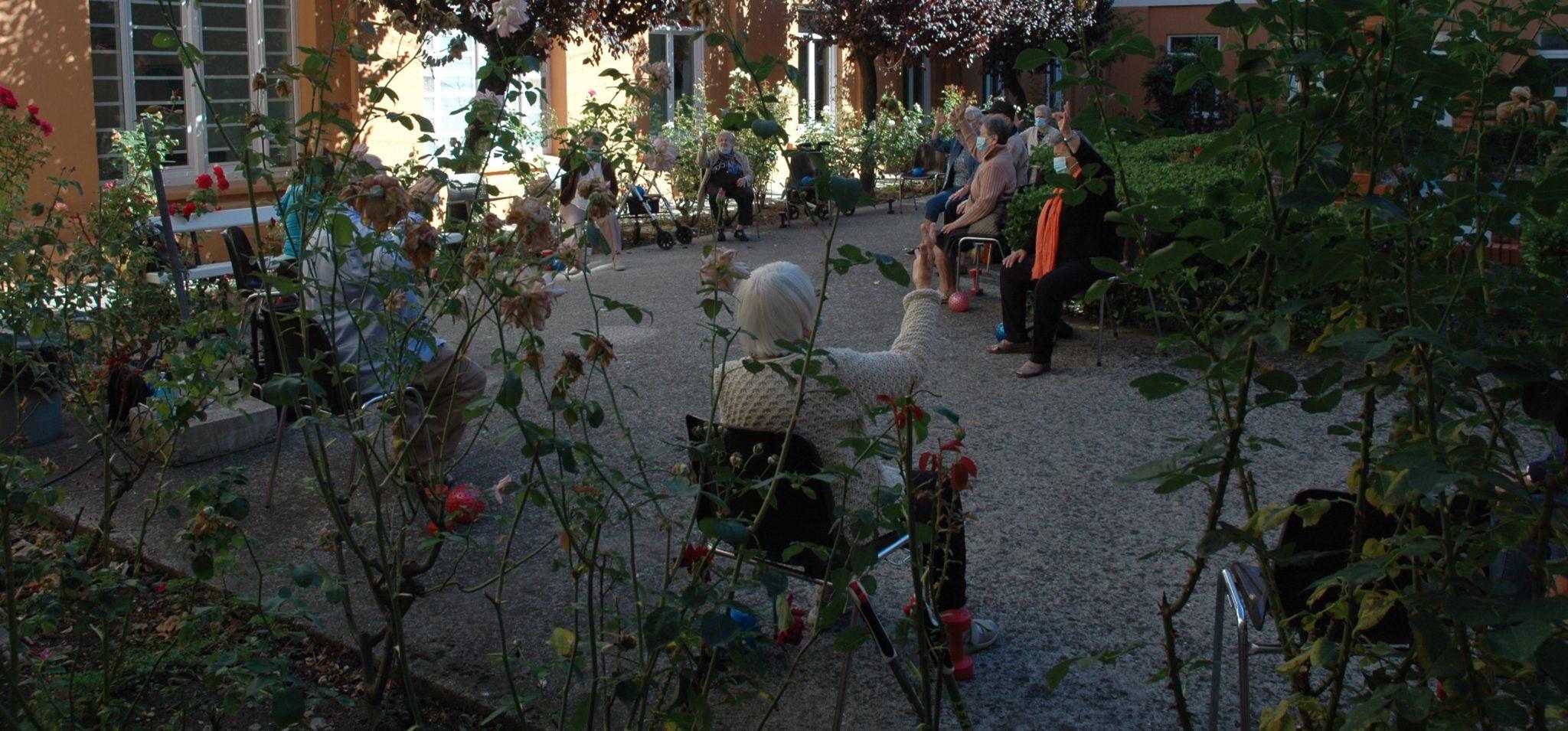 Personas residentes en la Casa de Misericordia, ejercitándose en el patio de la residencia
