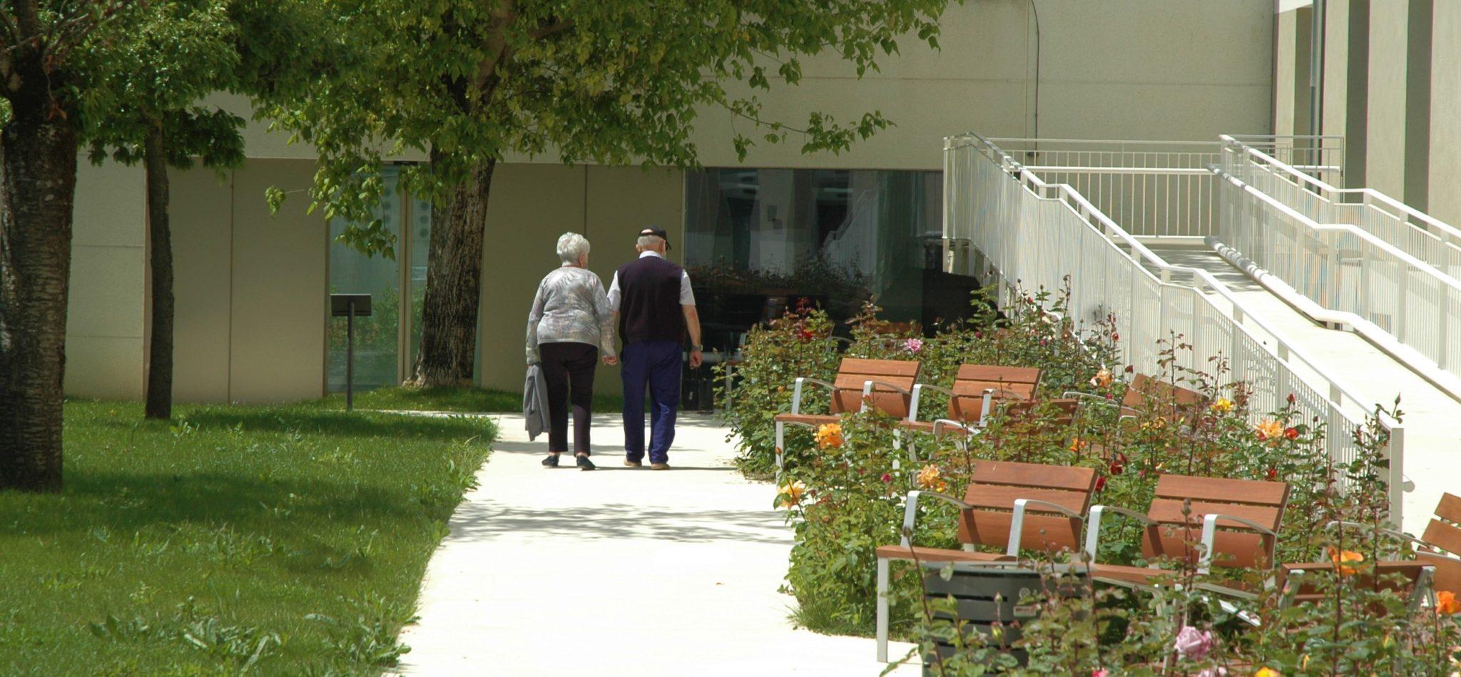 Dos personas caminan por el jardin de la Casa de Misericordia