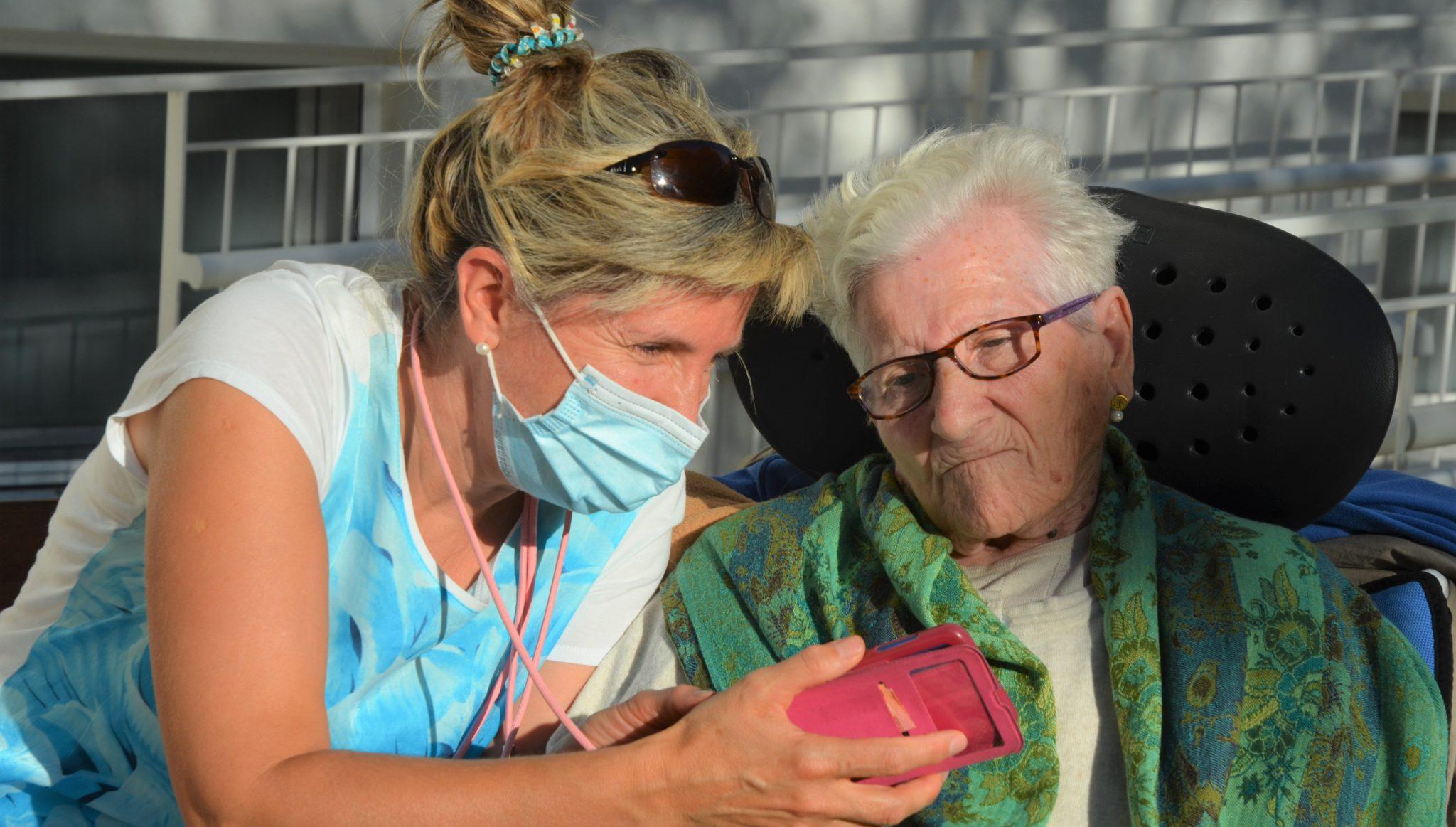 Un Familiar Y Una Persona Residente Miran Una Fotografía En El Teléfono Móvil En Un Jardin En La Casa De Misericordia